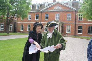 A lady in victorian costume, and C18 gentleman in front of a georgian house.