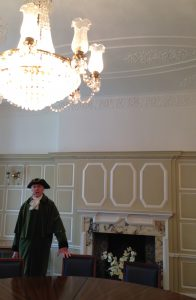 Gentleman in tricorn hat and green coat, in spacious, cream panelled room