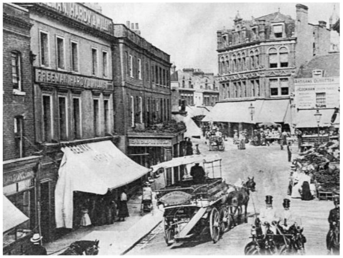 Shops with awnings and two storeys above them; horse drawn carts in street.