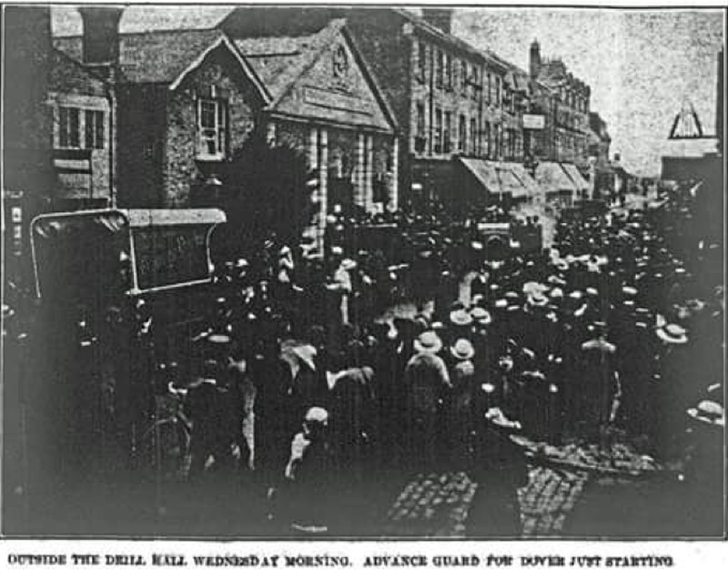 a street with soldiers assembled and people watching