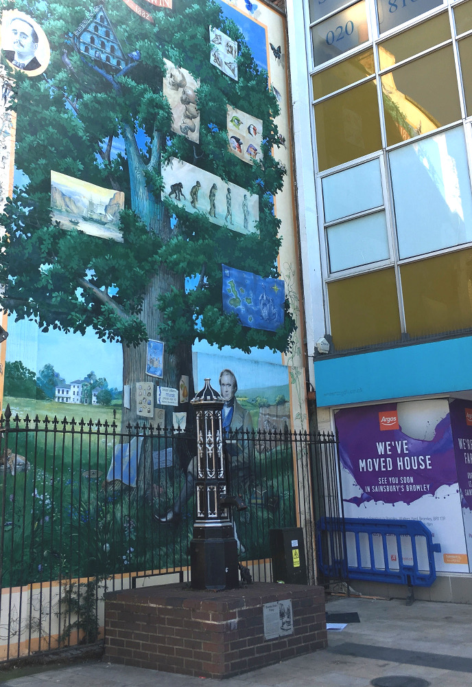 silver and black iron pump in front of mural with man and tree.