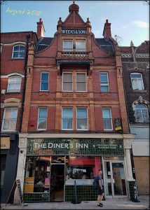 Green tile frontage of Civic Pride era, mid-3-storey-terrace, shop front