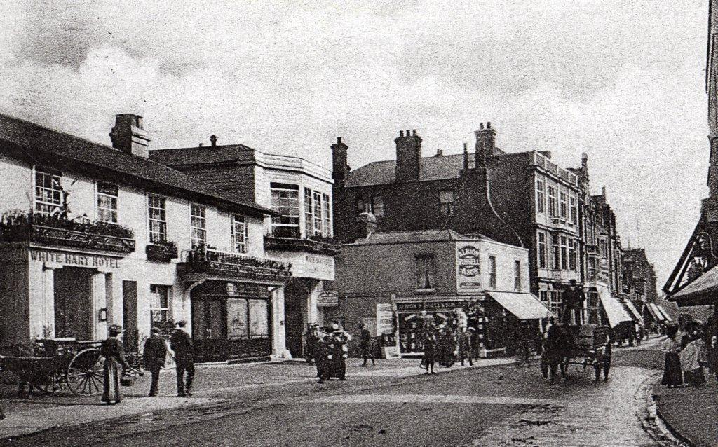 street scene from 1900s with hostelry on one side and hackney carraige
