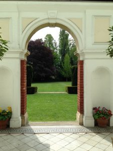 Classical arch through wihch is a view of the lawns.