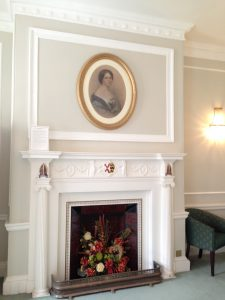 square design fireplace with oval lady's portrait above
