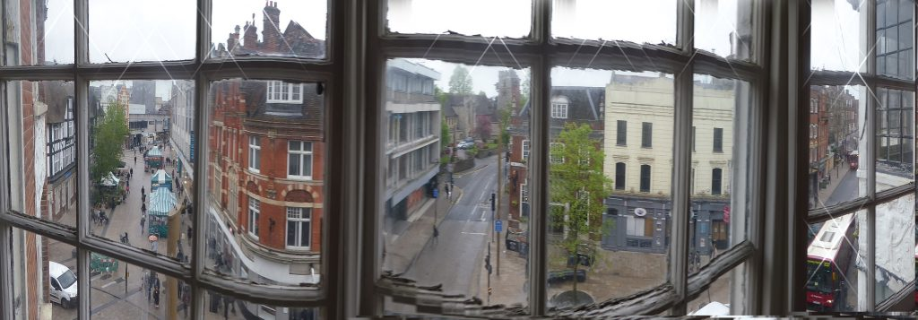 slightly distorted view of church tower through window panes