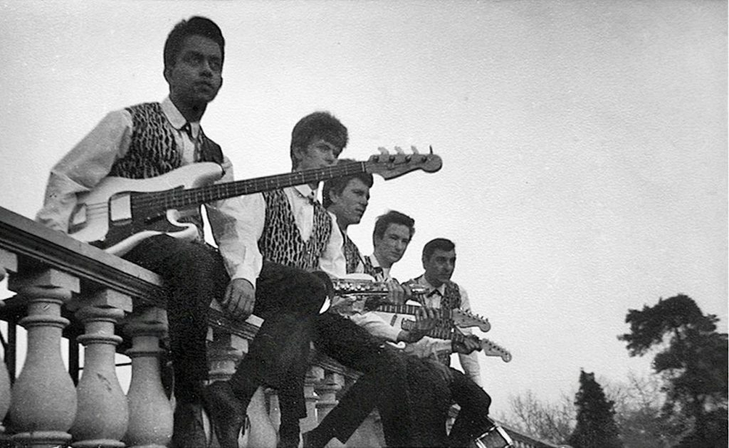 group of 1960s teens sitting on ballustrade