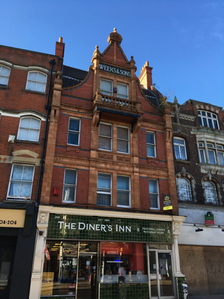 brick and stone shop with gable and balcony